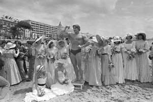 """FILE - In this May 20, 1977 file photo, Arnold Schwarzenegger shows off his body for an appreciative beach audience in Cannes, France, ahead of the presentation of his film """"Pumping Iron"""" at the Cannes Film Festival. The Cannes Film Festival officially gets underway on Wednesday, May 11, 2016 and as usual it's set to be one of the most dazzling events in the European entertainment calendar. The festival, in its 69th year, brings a mix of Hollywood A-listers and world cinema auteurs to the French Riviera. (AP Photo, File)"""