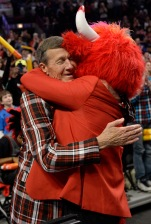 Craig Sager, gest a hug from Benny the Bull during a timeout of a game between the Chicago Bulls and the Oklahoma City Thunder, Thursday, March 5, 2015 in Chicago. Craig Sager returned to his familiar spot on the NBA sideline Thursday after being treated for leukemia. (AP Photo/David Banks)
