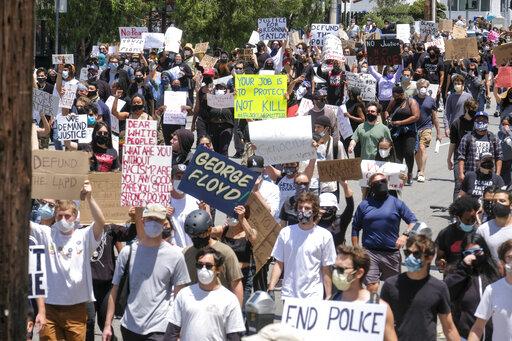 Protesters march on a street during a protest over the death of George Floyd, who died on Memorial Day after being taken into custody by Minneapolis police, in Los Angeles, Saturday, May 30, 2020. Floyd died after a police officer pressed his knee into his neck for several minutes even after he stopped moving and pleading for air. (AP Photo/Ringo H.W. Chiu)