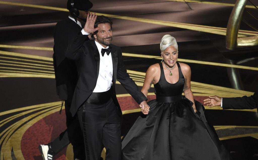 """Bradley Cooper, left, and Lady Gaga react to the audience after a performance of """"Shallow"""" from """"A Star is Born"""" at the Oscars"""