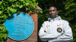 Eliud Kipchoge next to a plaque honoring Roger Bannister